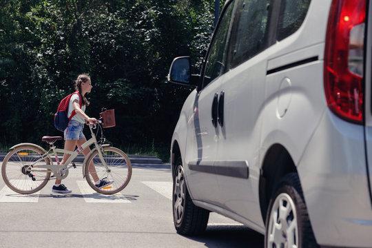 Teenage girl with backpack and bike on pedestrian crossing