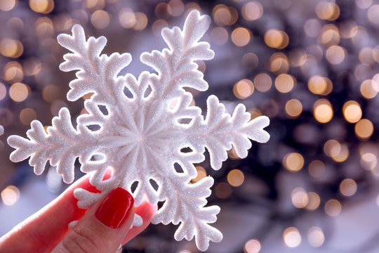 Female hand with xmas snowflake on blurred lights bokeh holiday background. Christmas..