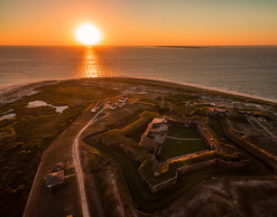 Stunning drone/aerial photograph of an ocean sunset over a Civil War fortress, Fort Morgan, & the Gulf of Mexico.  This fort is located near Gulf Shores, Alabama.  USA