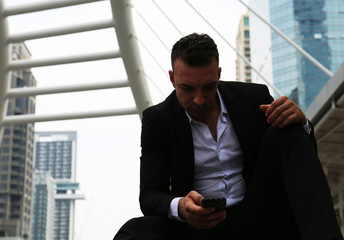 A business man sitting on walking street and looking mobile phone, blur mobile phone device.
