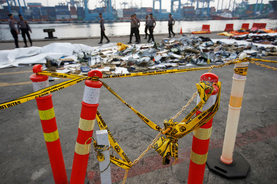 Police line is seen as Indonesian policemen walk near recovered debris and belongings of Lion Air flight JT610, that crashed into the sea, at Tanjung Priok port in Jakarta