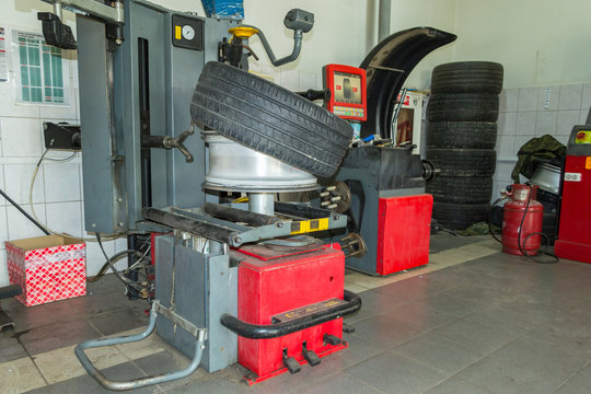 Summer car tire half taken from the disk to perform tire mounting and fitting on a special machine in the workshop for repairing vehicles before the start of the winter season