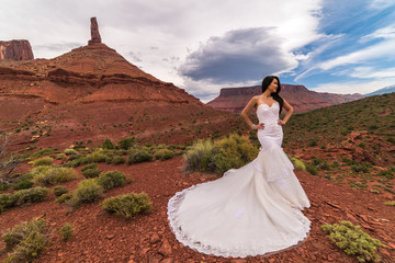 Asian/Vietnamese Bride in her wedding dress posing for wedding/engagement photo in the Utah desert near Moab.  Taken in front of Castleton Tower, Castle Valley.