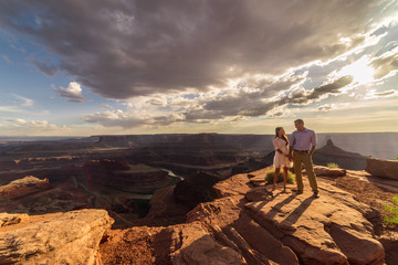Asian/Vietnamese Bride with White Groom.  Posing for engagement photos on the cliffs in Dead Horse Point State Park.  A vast scenic canyon overlook in the Utah desert, near Moab