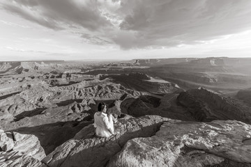 Asian/Vietnamese Bride posing for a Sunset engagement photo on the cliffs of the scenic Dead Horse Point State Park.  A massive overlook of the vast canyons of the Utah desert