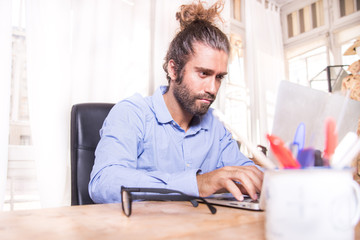 young man with long hair working with his laptop at home