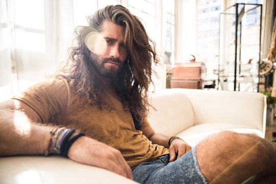 young man with long hair sitting on the sofa