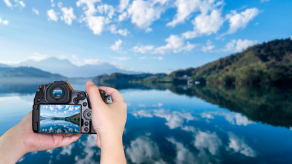 Woman hold digital camera on lake view 1