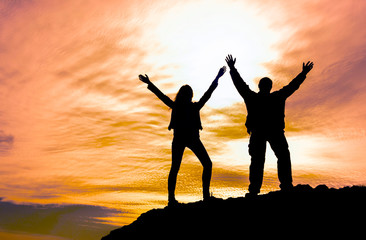 two people on top of the mountain holding hands up at sunset. achieving goals, winning, tourism, sports.