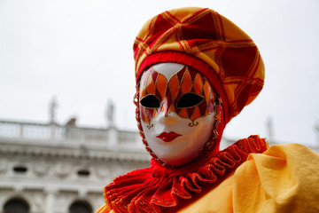 Carnival red-yellow mask and costume at the traditional festival in Venice, Italy