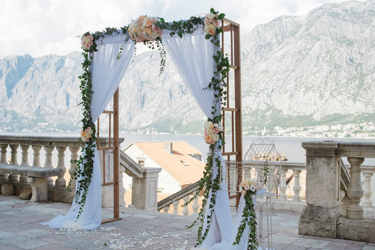 Beautiful wedding arch of flowers next to mountain and sea background
