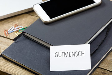 Gutmensch written on business card, office desktop with electronic devices