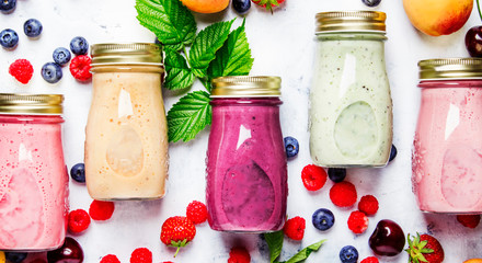 Healthy and useful colorful berry cokctalis, smoothies and milkshakes with yogurt, fresh fruit and berries on gray table, top view