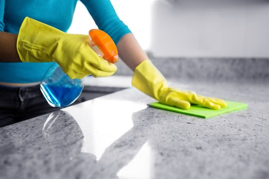 Mid section of woman cleaning kitchen counter