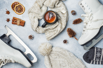 Winter vacation concept. Skates warm clothes, Cup of hot tea with fragrant spices on grey background.