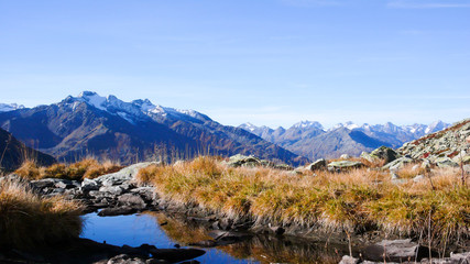 Wall Mural - wild and picturesque horizontal mountain landscape in the Swiss Alps on a beautiful day in late autumn with mountains and a great view and a small lake in the foreground