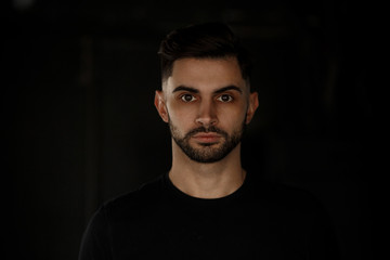 Close-up portrait of an attractive young handsome man with a stylish beard standing on a dark background, dressed in a black t-shirt.
