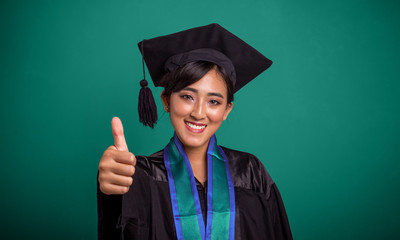 Beautiful smiling graduate student thumb up, over green banner