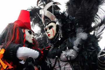 Carnival pair black-red mask and costume at the traditional festival in Venice, Italy