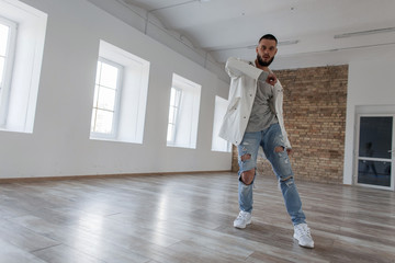Attractive dancer in a fashionable jacket and stylish ripped jeans dancing in the studio