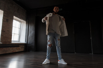Stylish handsome young man in fashion white jacket with blue ripped trendy jeans with sneakers posing in a dark studio
