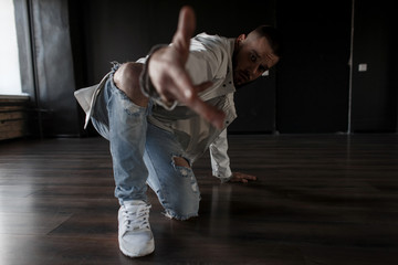 Fashionable stylish handsome young male dancer in a white jacket and blue ripped jeans with sneakers performs in a dark dance studio. Pulls hand into the camera