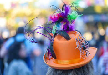 Unrecognizable woman wearing orange top hat decorated for Dia de los Muertos/Day of the Dead/Halloween