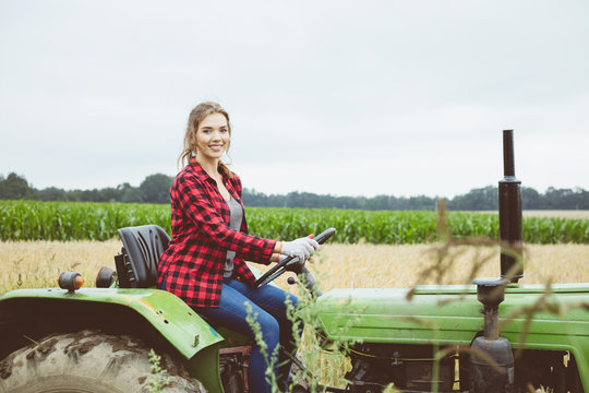 Outdoor shot of young woman sitting on tractor