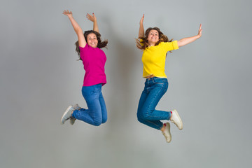 Two Twin Sisters Jumping on Gray Background
