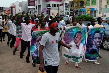 Members of the Islamic Movement of Nigeria gesture during a march to demand the release of their Nigerian Shi'ite leader Ibrahim Zakzaky, along a street in Abuja