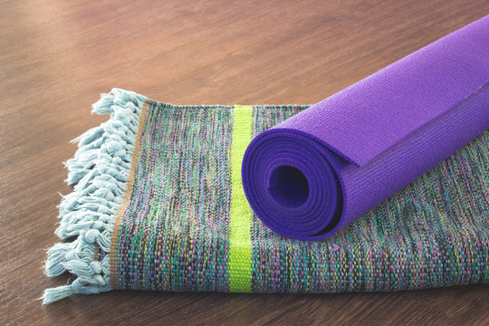 Purple yoga mat on top of colorful cotton mat. Studio material on wooden floor. Practice, healthy lifestyle concepts