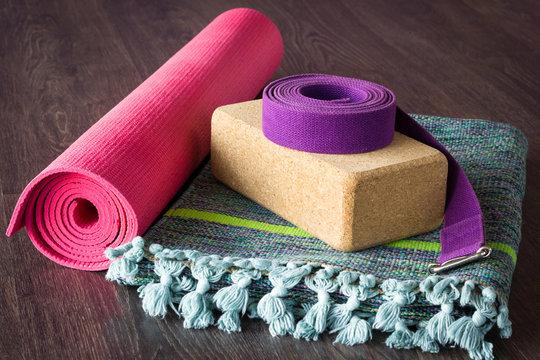 Yoga studio props selection on wooden floor. Pink mat, cork brick, purple belt and colorful cotton mat