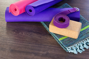 Yoga studio set of props on wooden floor. Pink and purple mats, cork brick, belt and colorful cotton mat