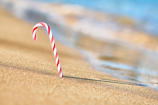 Christmas Candy cane on the beach. Sea view holiday vacation concept