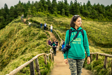 Young woman in khaki clothing is standing on the most popular place on Azores islands - Miradouro da Boca do Inferno. On the way to view point. Portugal, Sao Miguel.
