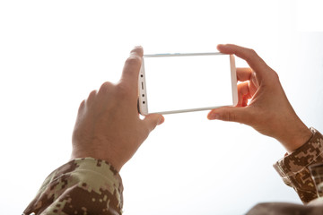 Young soldier holding a mobile phone with blank screen on white background