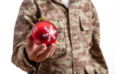 Young soldier holding a red christmas ball standing on white background