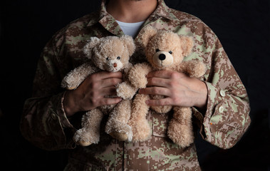 Young soldier holding a teddy bear standing on black background