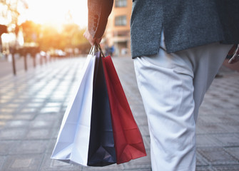 Concept of man shopping and holding bags, closeup images. Close up of paper shopping bags in male hand.