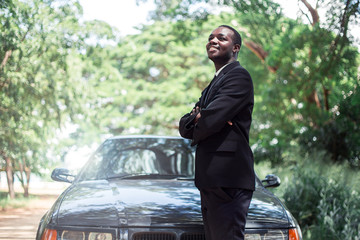 African Businessman in suit standing near car with green natural background.