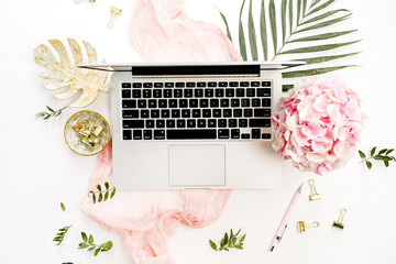 Woman home office desk with laptop, pink hydrangea flowers bouquet, tropical palm leaf, pastel blanket, monstera leaf plate and accessories on white background. Flat lay, top view rose gold workspace.