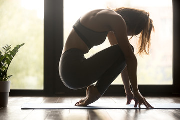 Young sporty yogi woman practicing yoga, doing feet strengthening exercise, healing physical therapy pose, working out wearing sportswear grey pants and top, indoor full length, yoga studio, side view