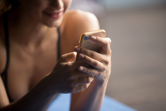 Young attractive woman after practicing yoga, relaxing on yoga mat, using app, making a call, texting, smiling and enjoying a rest, looking at smartphone, messaging, indoor close up of hands and phone