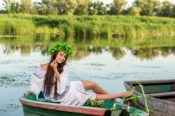 The nymph with long dark hair in a white vintage dress sitting in a boat in the middle of the river.