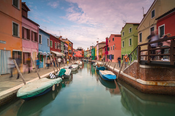 View on Rio Di San Mauro in Burano with passing people at sunset,long exposure photo.