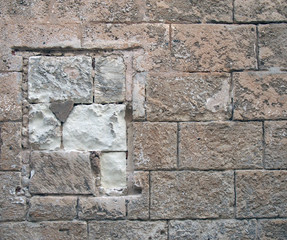 old stone wall built of large rough textured brown blocks with a repaired blocked up window