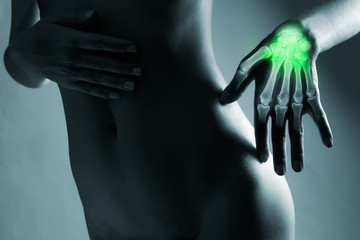 Human hand in x-ray, on gray background. The hand is highlighted by green colour.