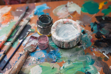 Oil paints and paint brushes on a palette, in the studio of artist.