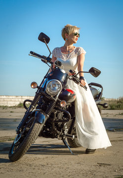 young woman in a bridal wedding dress and sunglasses on a motorcycle