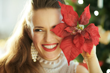 housewife with red poinsettia looking aside near Christmas tree
